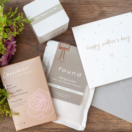 Chocobien CBD chocolate, CBD tea, CBD bath salts and Mother's Day card laying on a table